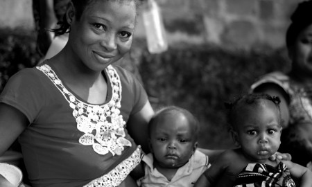 A woman and her two children wait outside a health clinic in M'banza Congo, Zaíre province, to be seen by a health technician.
