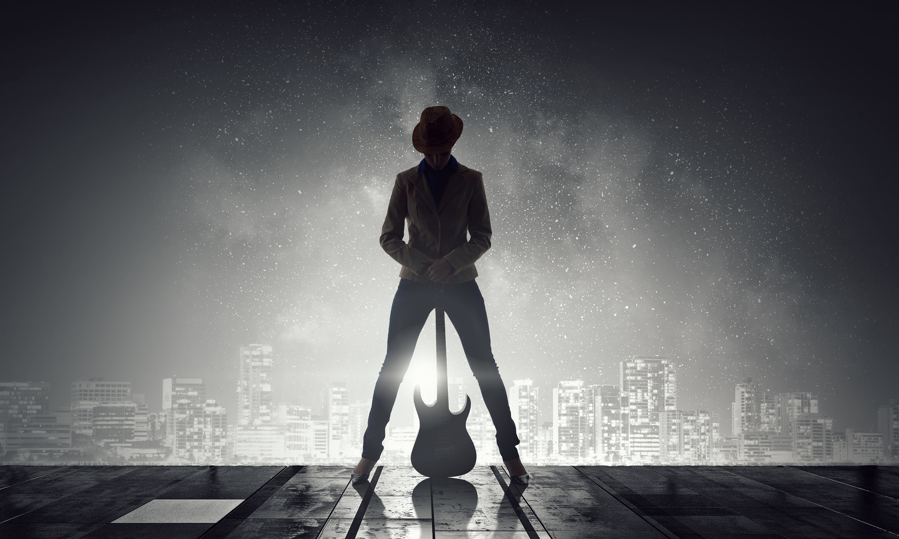 Silhouette of woman with guitar against night city background