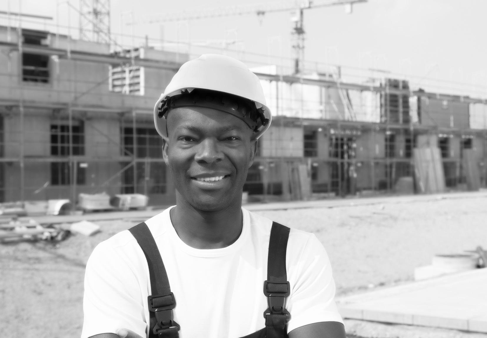Attraktiver afrikanischer Bauarbeiter auf der Baustelle