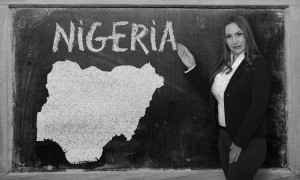 Successful, beautiful and confident young woman showing map of nigeria on blackboard for presentation, marketing research and tourist advertising